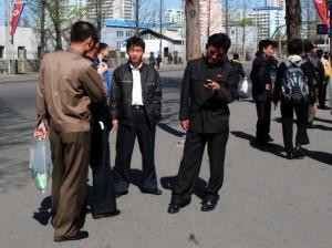5月1日,平壤街头,一位市民正在查看手机